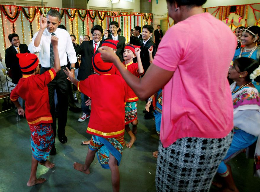 President Obama and first lady Michelle Obama dance with students as they celebrate Diwali, an Indian festival, during a visit to Holy Name High School in Mumbai on Sunday. After India, they will move on to Indonesia, South Korea and Japan. (Associated Press)