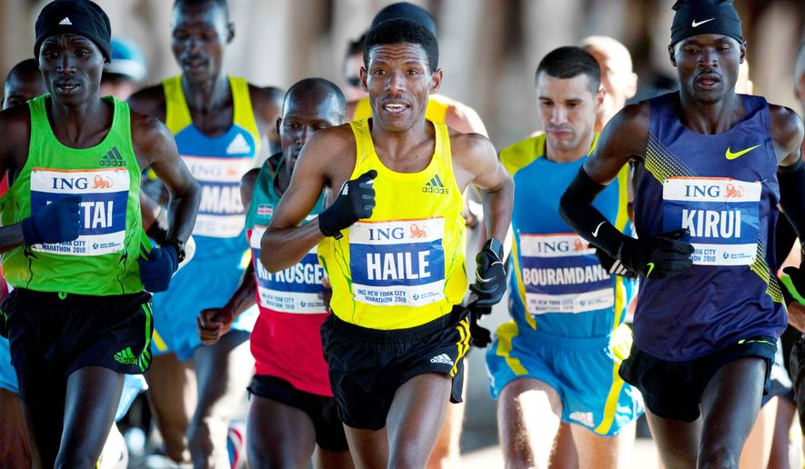 World record holder Haile Gebrselassie of Ethiopia (center) runs with the men's pack during the New York City Marathon on Sunday. He announced his retirement after dropping out of the race with a right knee injury at the 16th mile. (Associated Press)