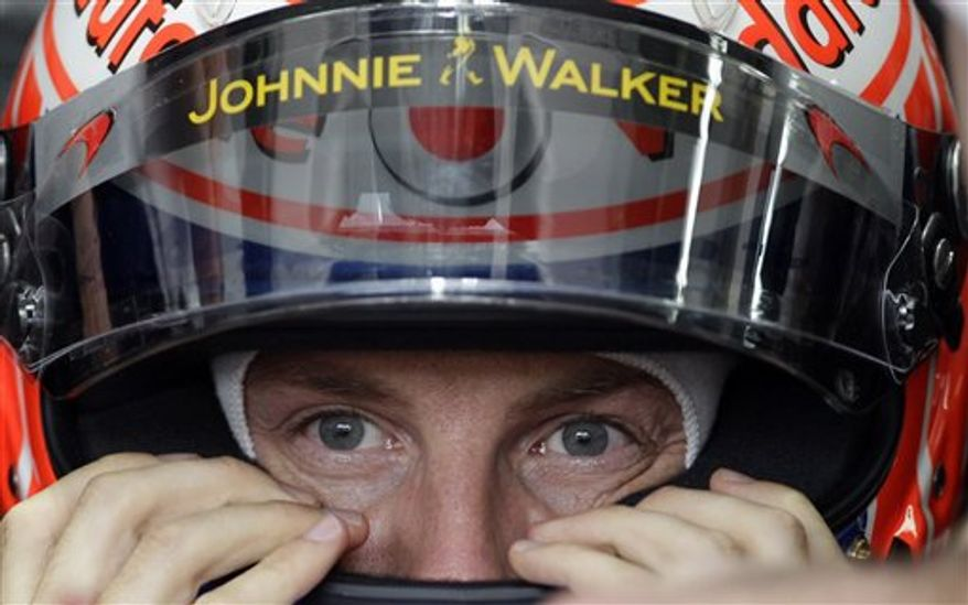McLaren driver Formula One champion Jenson Button of Britain fits his helmet during the second free practice for the Brazilian Formula One Grand Prix at the Interlagos race track in Sao Paulo, Brazil, Friday, Nov. 5, 2010. Armed men tried to attack the car carrying Button as he left the track at the Brazilian Grand Prix on Saturday, the McLaren team said. McLaren said Button was driven away from danger and nobody was hurt in the incident near the Interlagos circuit. (AP Photo/Silvia Izquierdo)