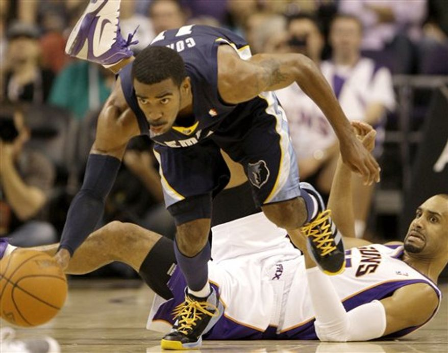 Memphis Grizzlies' Rudy Gay, left, charges into Phoenix Suns' Hakim Warrick (21) for a foul as Suns' Grant Hill looks on during the second quarter of an NBA basketball game Friday, Nov. 5, 2010. (AP Photo/Ross D. Franklin)