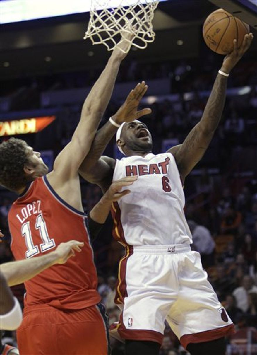 Miami Heat forward LeBron James, center, prepares to dunk the ball on a pass from Dwyane Wade (3) in the third quarter against the New Jersey Nets during an NBA basketball game in Miami, Saturday, Nov. 6, 2010. At left is Nets forward Kris Humphries, and at right is Jordan Farmer. (AP Photo/Lynne Sladky)