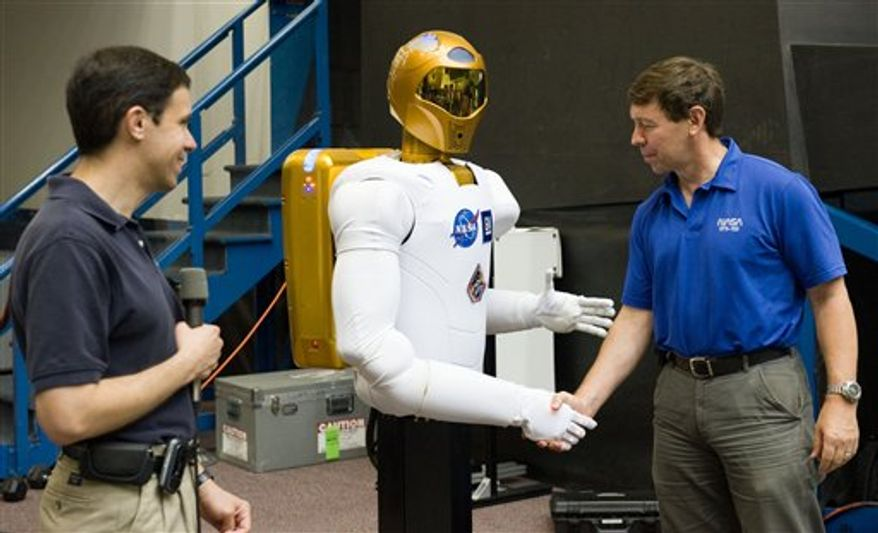 In this March 3, 2011 photo provided by NASA, astronauts Eric Boe, left, and Scott Kelly move the crate containing Robonaut 2, better known as R2, the first humanoid robot in space, at the International Space Station. The 220-mile-high (354-kilometer-high) unveiling of R2, the first humanoid robot in space, is being moved up at the urging of the president of the United States. Astronaut Catherine Coleman said Friday, March 4, 2011 that she and the 11 other humans aboard the shuttle-station complex want to get R2 out of its packing material as soon as possible. R2, flew to the International Space Station aboard Discovery and will stay behind when the shuttle leaves Monday. (AP Photo/ESA/NASA)