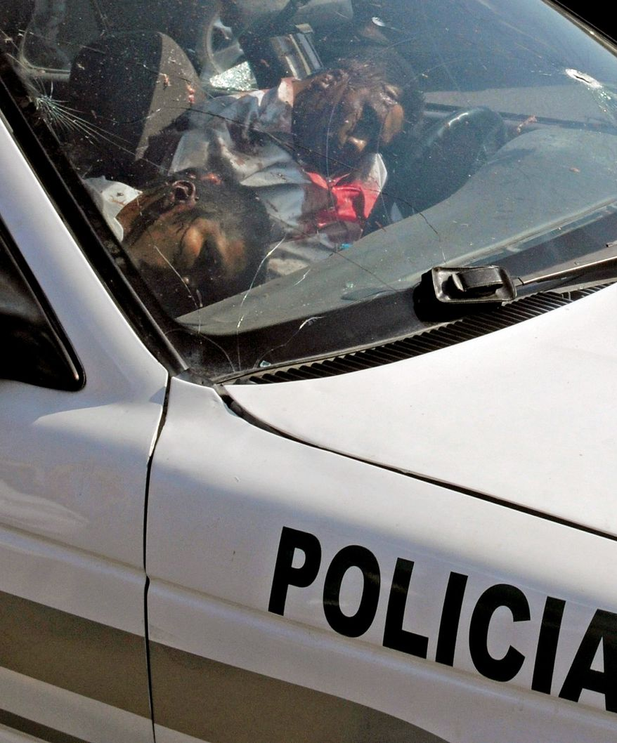 The bodies of two dead traffic police officers remain in their patrol car in Acapulco on Thursday. Gunmen killed four police officers the day after a grave holding at least 18 bodies was found. (Associated Press)
