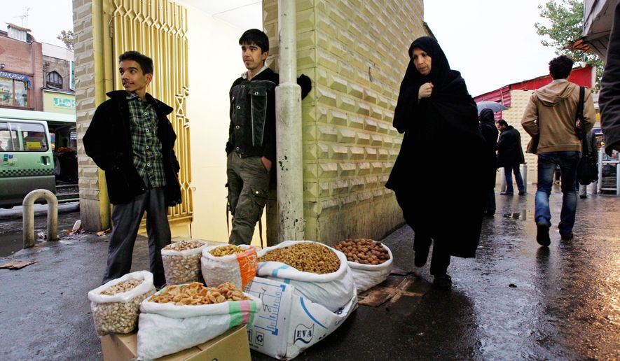 Vendor Amir Jamali (center) waits for customers Tuesday in downtown Tehran. The government has started cutting subsidies for fuel and food staples, causing prices to increase dramatically. (Associated Press)
