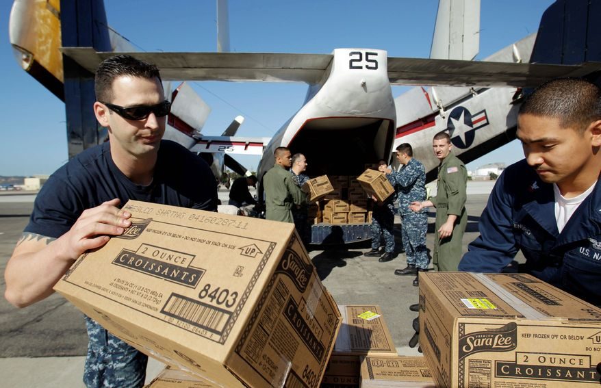 Navy officials load boxes of croissants onto a plane for the Carnival Splendor cruise ship on Tuesday in San Diego. The navy is sending more than 70,000 pounds of food to the ship. (Associated Press)