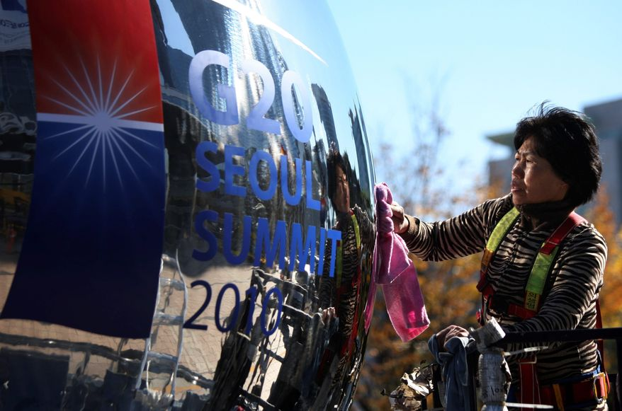 A woman polishes a chrome globe at the entrance to the venue of the upcoming G-20 summit on Tuesday in Seoul. The U.S. already is signaling that it may tone down its demands for action by China, Germany and other countries with chronic surpluses. (Associated Press)
