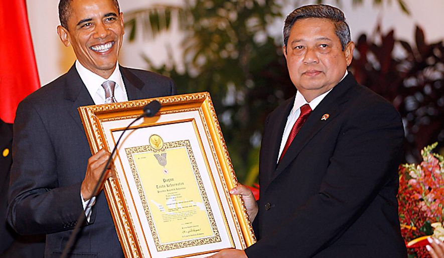 President Barack Obama accepts an award on behalf of his late mother Stanley Ann Dunham for her work in Indonesia, from Indonesian President Susilo Bambang Yudhoyono, during the state dinner at the Istana Negara in Jakarta, Indonesia, Tuesday, Nov. 9, 2010. (AP Photo/Charles Dharapak)