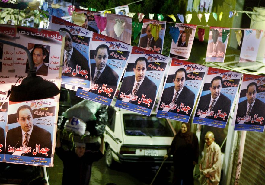 """Egyptians walk under posters touting Gamal Mubarak, the son of President Hosni Mubarak, as the country's next leader, in August in Cairo. The Arabic text reads: """"Gamal for all Egyptians."""" The son may have to wait, however, as the elder Mr. Mubarak is expected to run for another term next year. (Associated Press)"""