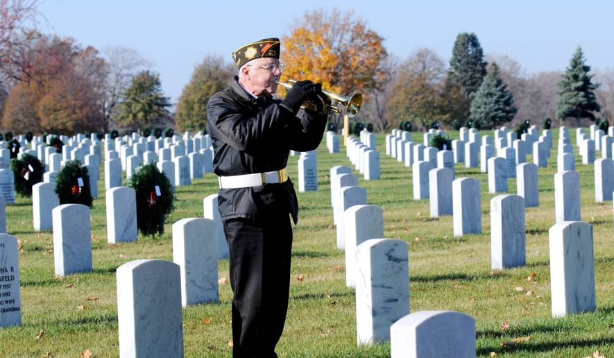 """Veteran Clarence Kraemer plays """"Taps"""" during a funeral for a veteran at Fort Snelling National Cemetery in Bloomington, Minn. Every weekday, 12 months a year, the men of the Fort Snelling Memorial Rifle Squad are out in force and in formation, paying tribute to veterans being laid to rest. (Associated Press)"""