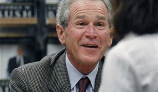 """Former President George W. Bush signs a copy of his book """"Decision Points"""" at a store near his Dallas home, Tuesday, Nov. 9, 2010. (AP Photo/LM Otero)"""