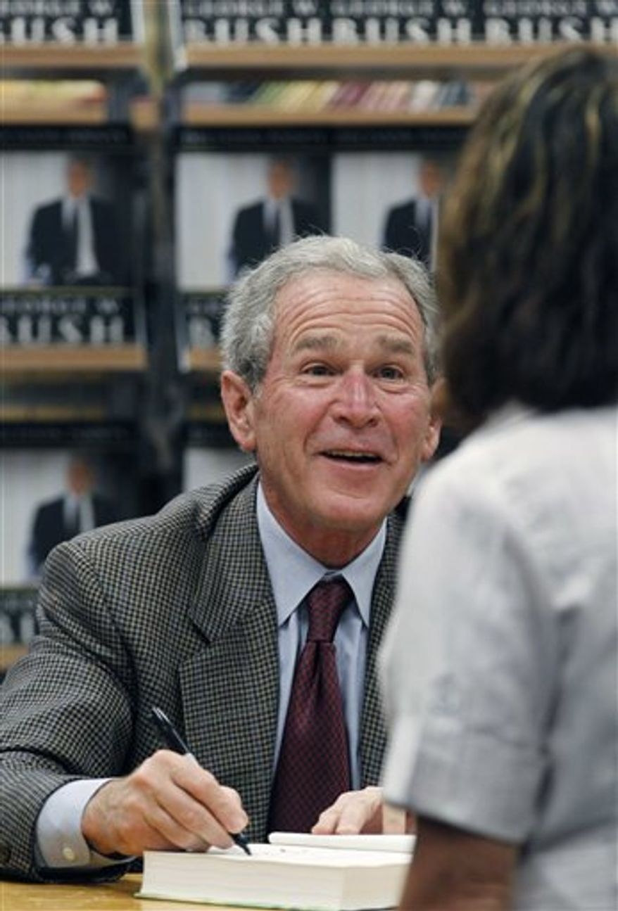 "Former President George W. Bush signs a copy of his book ""Decision Points"" at a store near his Dallas home, Tuesday, Nov. 9, 2010. (AP Photo/LM Otero)"