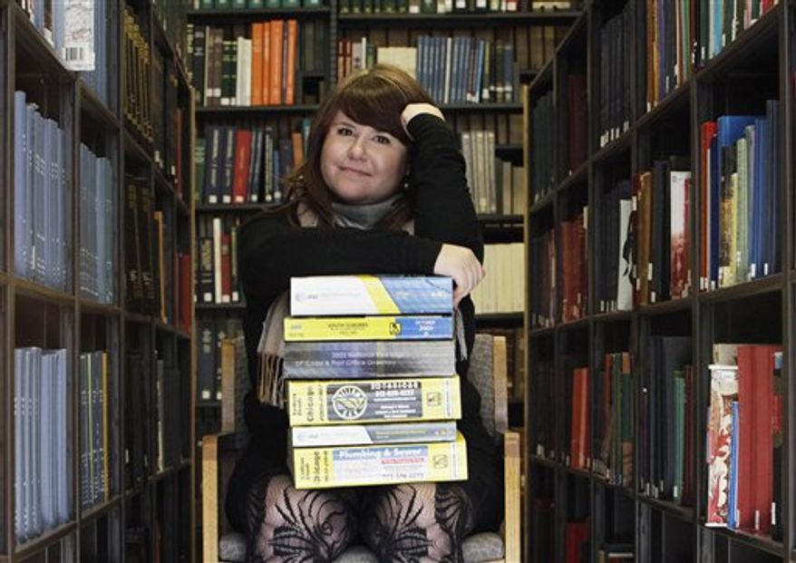 This photo taken Tuesday, Nov. 9, 2010, shows Emily Goodmann sitting with a small stack of phone books at the Northwestern University Library in Evanston, Ill. Goodmann is a doctoral student who is doing her dissertation on the history of the telephone book. (AP Photo/Charles Rex Arbogast)