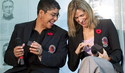 Hockey Hall of Fame inductees Angela James, left, Dino Ciccarelli and Cammi Granato, right, show off their rings after being presented with them at the hall in Toronto on Monday,  Nov. 8, 2010. (AP Photo/The Canadian Press, Frank Gunn)