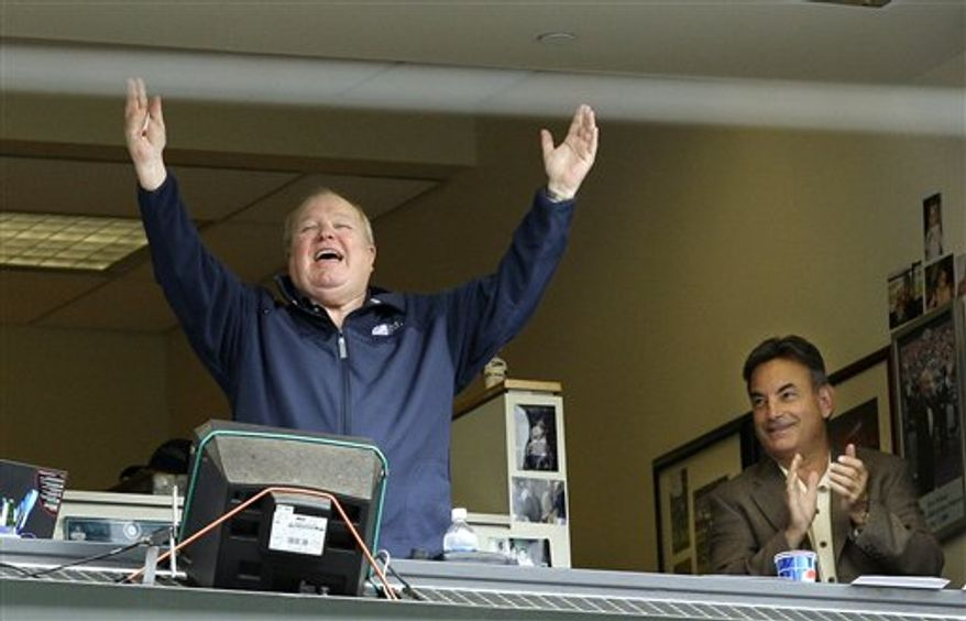 FILE - In this July 23, 2008, file photo, broadcaster Dave Niehaus raises his arms in the booth as he is introduced to the crowd during a baseball game between the Seattle Mariners and the Boston Red Sox, as fellow broadcaster Rick Rizzs applauds at right in Seattle. Niehaus, the legendary and beloved voice of the Mariners from their inception in 1977 through the final game of the 2010 season, has died, the ballclub confirmed on Wednesday, Nov. 10, 2010. Niehaus, who received the Ford Frick Award at the Hall of Fame induction ceremony in 2008, was 75. (AP Photo/Elaine Thompson, File)