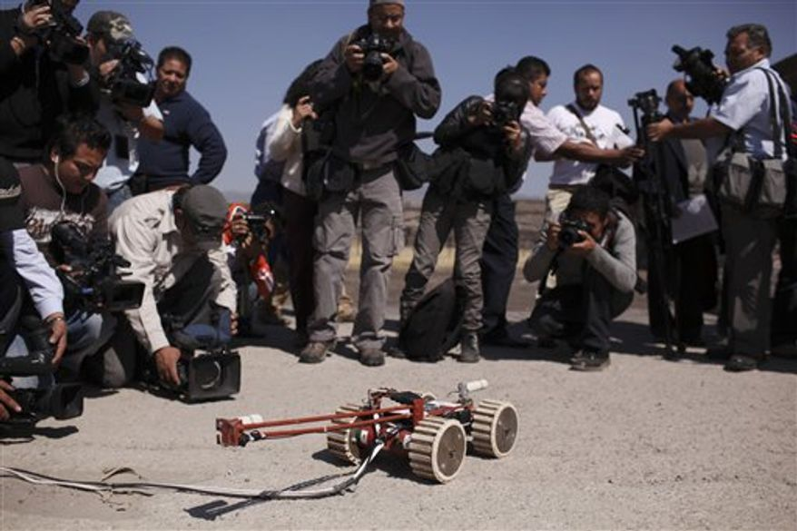 A robot used to explore ruins in Teotihuacan, Mexico, sits on the ground Wednesday, Nov. 10, 2010. The small foot-wide wheeled vehicle, able to record video, entered a 2,000-year-old tunnel found earlier this year under the ruins of the temples of Teotihuacan. (AP Photo/Alexandre Meneghini)