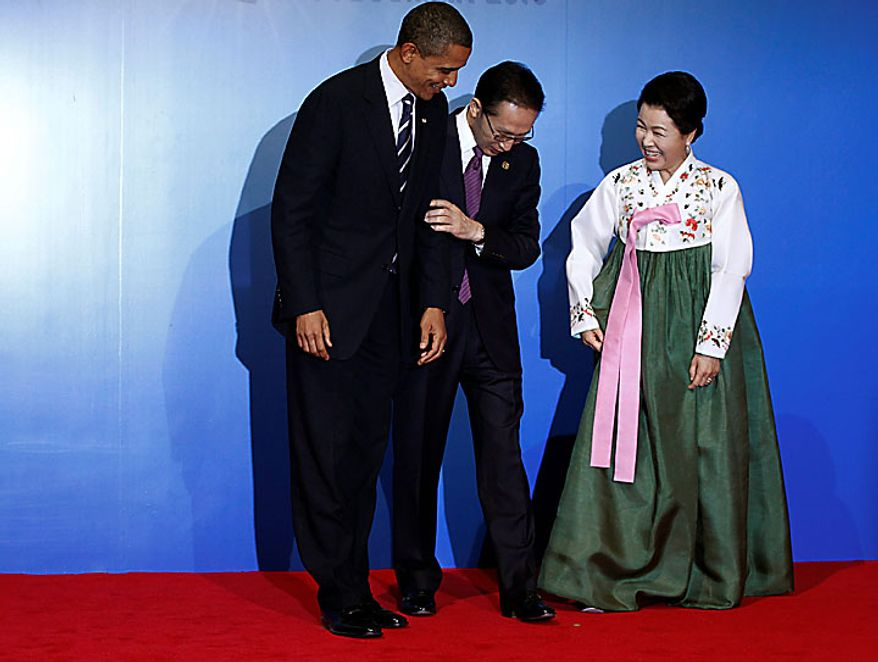 South Korean President Lee Myun-bak, center, and his wife Kim Yoon-ok, right, reposition President Barack Obama for a photo for the official arrival and reception at the G-20 summit in Seoul, South Korea, Thursday, Nov. 11, 2010. (AP Photo/Charles Dharapak)