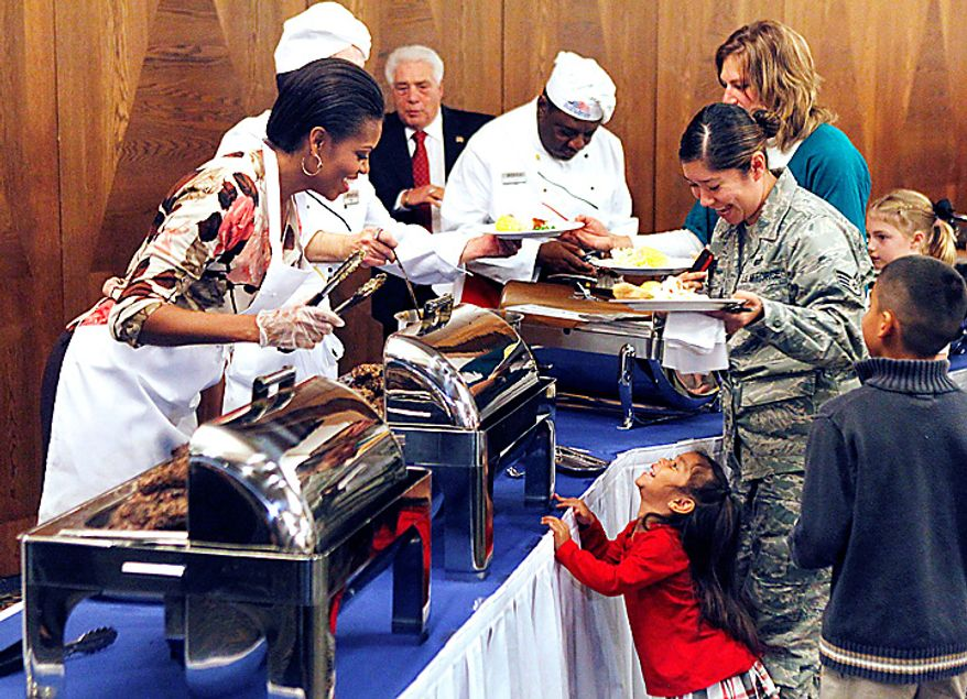 The first lady of the United States Michelle Obama (left) serves food to U.S. airmen and their relatives at Ramstein Airbase in Ramstein, Germany, on Nov. 11, 2010. Michelle Obama makes a series of stops within the Kaiserslautern Military Community on Veterans Day to thank U.S. servicemen and women for their work. (Associated Press)