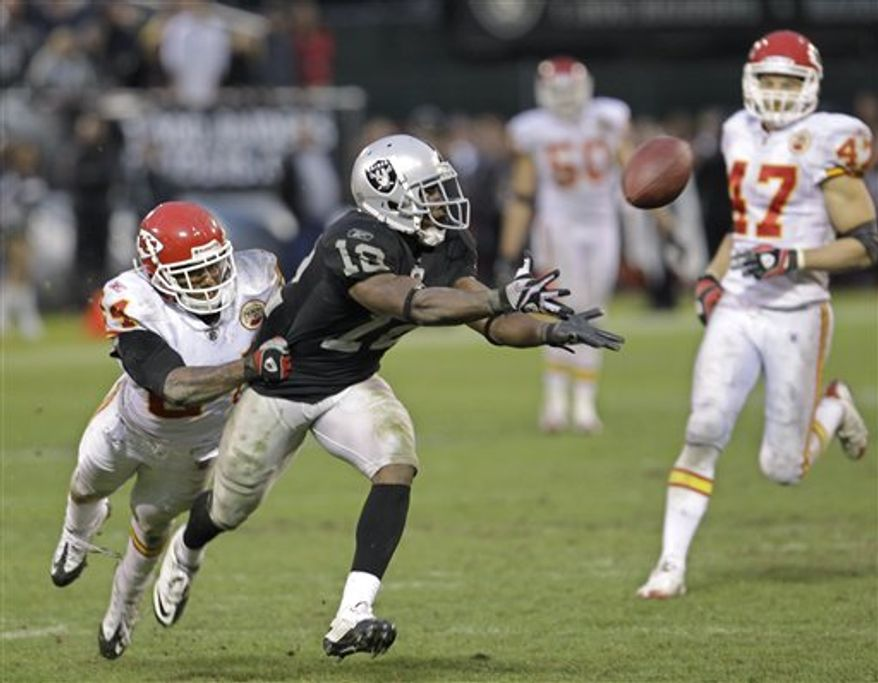 Oakland Raiders wide receiver Jacoby Ford (12) catches a 47 yard pass in front of Kansas City Chiefs cornerback Brandon Flowers (24) to help set up a field in overtime for the Raiders to defeat the Chiefs 23-20 in an NFL football game in Oakland, Calif., Sunday, Nov. 7, 2010. (AP Photo/Paul Sakuma)