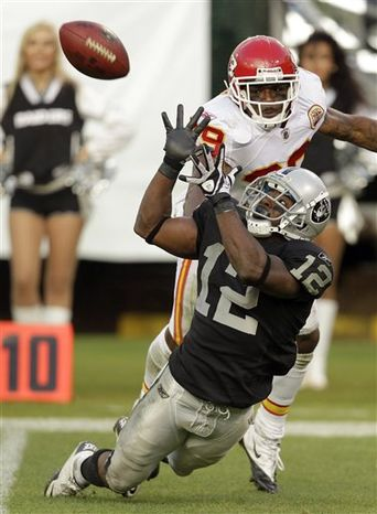 Oakland Raiders wide receiver Jacoby Ford (12) catches a pass over Kansas City Chiefs cornerback Brandon Flowers during the fourth quarter of an NFL football game in Oakland, Calif., Sunday, Nov. 7, 2010. Oakland won 23-20 in overtime. (AP Photo/Paul Sakuma)