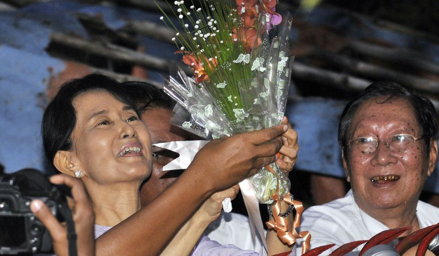 Burma's pro-democracy leader Aung San Suu Kyi, left, smiles after she received flowers from her supporters as she stands at the gate of her home Saturday, Nov. 13, 2010, in Rangoon, Burma. Burma's military government freed its archrival Suu Kyi on Saturday after her latest term of detention expired. The man on her right is Nyan Win, spokesman of her National League for Democracy. (AP Photo/Khin Maung Win)