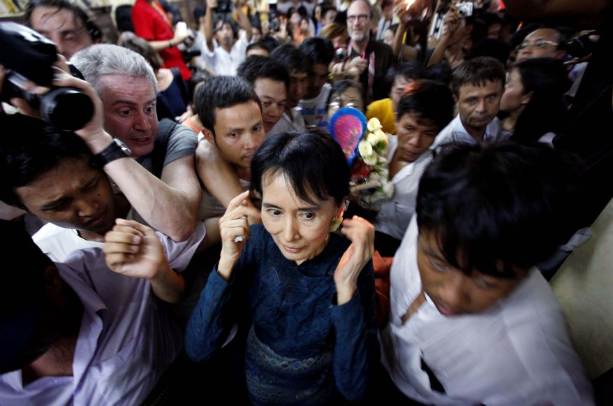 ASSOCIATED PRESS FREE AGAIN: Burmese pro-democracy icon Aung San Suu Kyi leaves her political party office Sunday through supporters in Rangoon after her first news conference since being released from her latest house arrest.