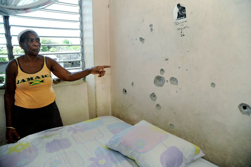 ASSOCIATED PRESS PHOTOGRAPHS Joan McCarthy shows a bullet-scarred wall in her Tivoli Gardens apartment in Kingston, Jamaica, where she says police and military officers shot her son-in-law and nephew while seeking a fugitive gang boss. Neither man has been seen since.