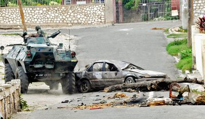 A Jamaica Defense Force armored vehicle makes its way in Hannah Town, West Kingston, in May while seeking the fugitive drug kingpin. Residents set up barricades to bar police from the slums.