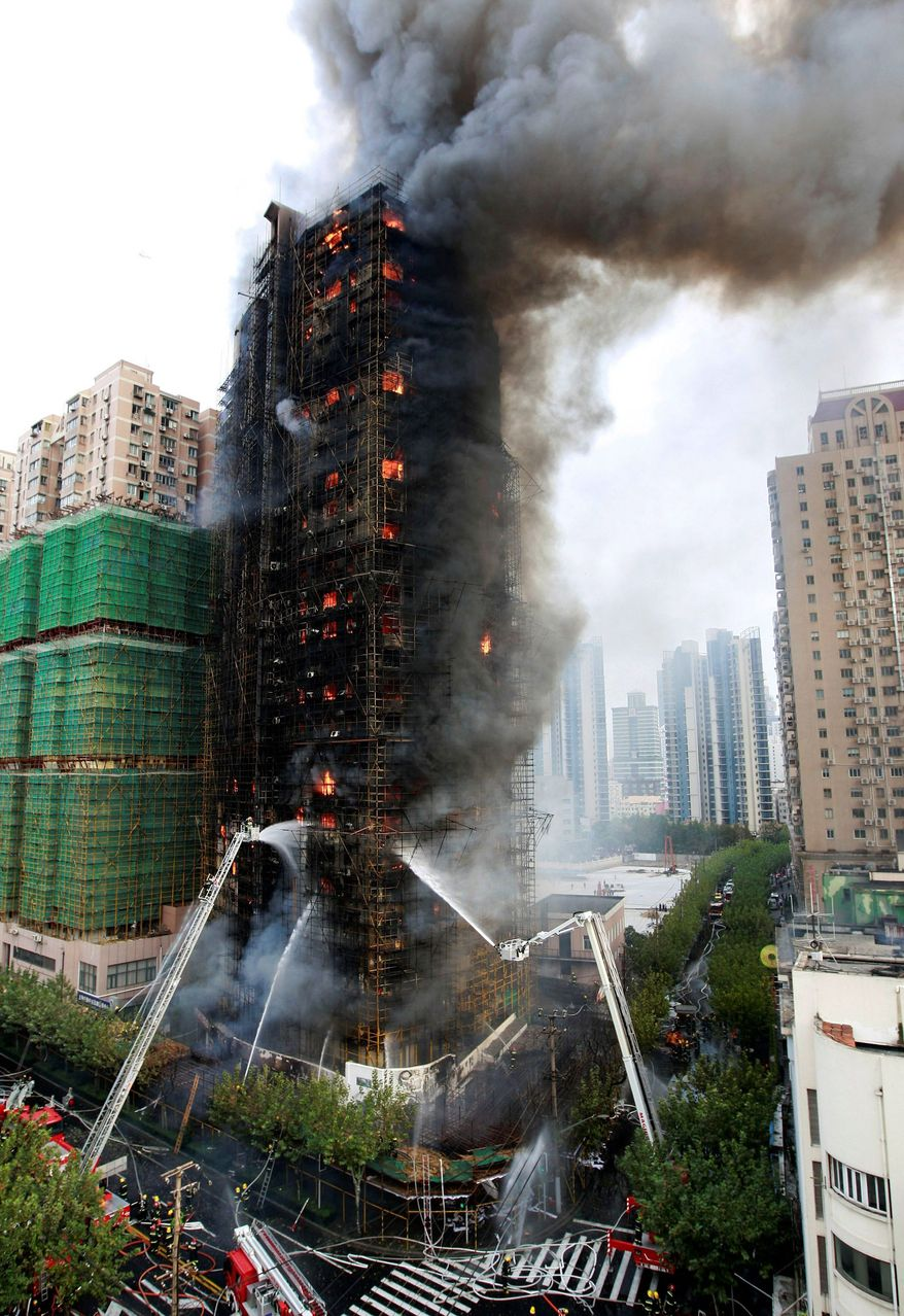 ASSOCIATED PRESS Firefighters spray an apartment building on fire in Shanghai on Monday. At least 42 people died in the blaze.