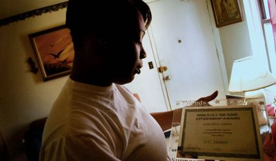 J.M. EDDINS JR./THE WASHINGTON TIMES LaVonne Abney shows a citizenship award from Ballou Stay Senior High School that her dead son, Chicquelo, earned there. Though Chicquelo had graduated from Canyon State Academy, handled living in a group home and took night classes at Ballou, he still faced a major challenge of living in a violent, drug-plagued neighborhood.