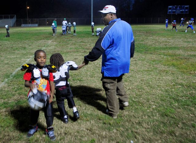 "Curtis ""Coach Peedy"" Monroe leads practice of the Benning Terrace Pop Warner football team in Washington. The coach tried to save Chicquelo Abney from the streets by keeping him involved in football. His Pop Warner football coaches recall that he took his performance on the field - and his appearance - seriously. (J.M. EDDINS JR./THE WASHINGTON TIMES/File)"