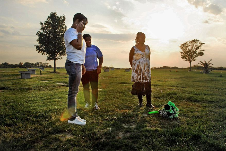 J.M. EDDINS JR./THE WASHINGTON TIMES NOT FORGOTTEN: LaVonne Abney (left), with her mother, Ruth Wheeler (right), and LaVonne's niece, Leshawn Wheeler, 15, visit the Landover, Md., grave of Chicquelo Abney on the first anniversary of his death.