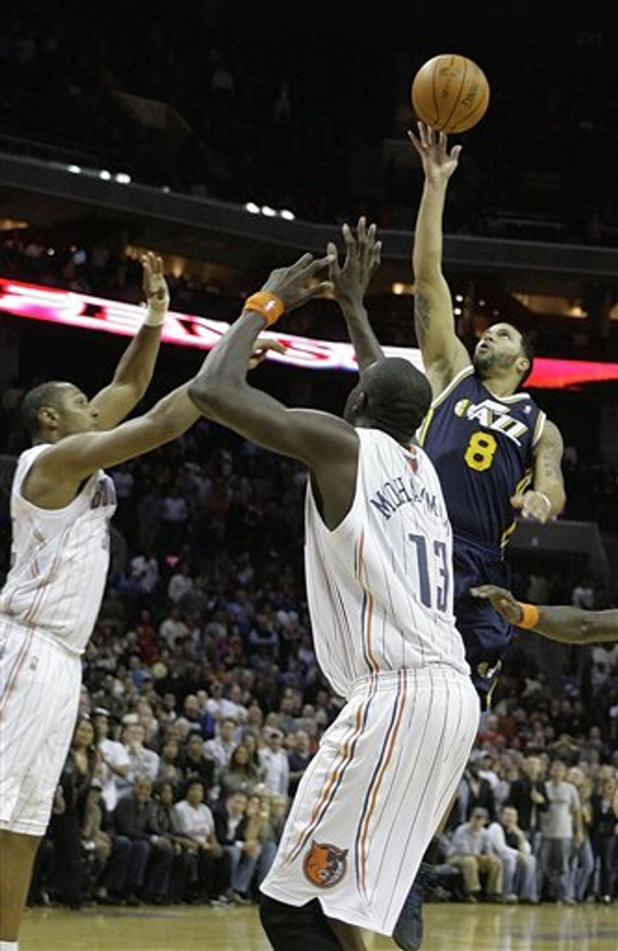 Utah Jazz's Deron Williams (8) puts up the winning shot over Charlotte Bobcats' Boris Diaw, left, and Nazr Mohammed (13) during the second half of an NBA basketball game on Saturday, Nov. 13, 2010, in Charlotte, N.C. Utah defeated Charlotte 96-95. (AP Photo/Rick Havner)