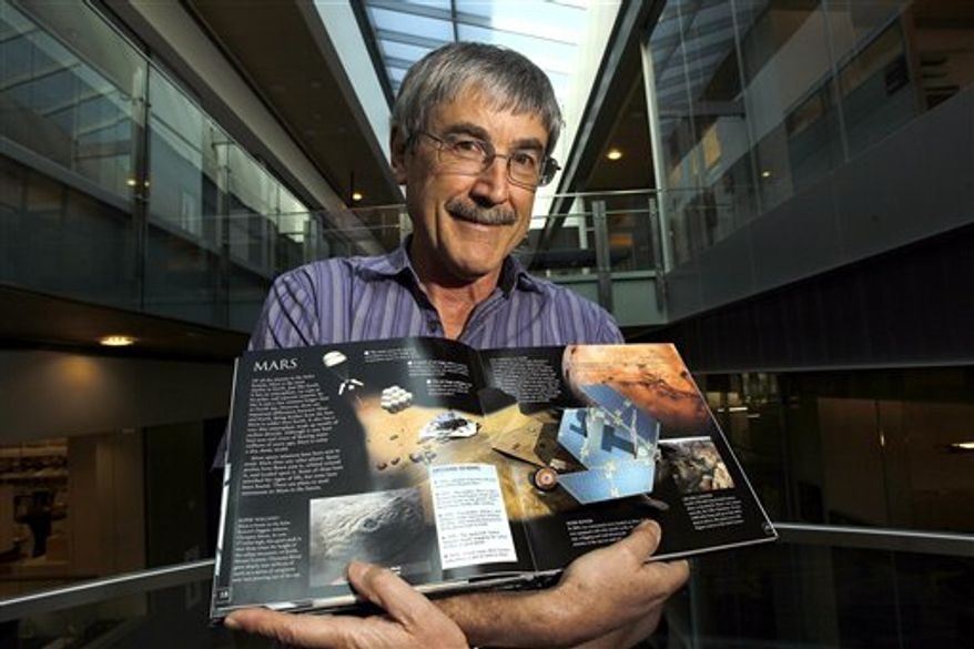 In this photo taken Oct. 28, 2010, Dr. Paul Davies, of Arizona State University, holds a book on Mars as he stands in the atrium of the Biodesign Institute building on the ASU campus Thursday, Oct. 28, 2010, in Tempe, Ariz.  Davies is one of two scientists that are proposing we send volunteers to Mars and leave them there.  Dr. Davies says the mission would mark the beginning of long-term human colonization of Mars, with numerous follow-up trips. The colleagues contend one-way missions could happen a lot quicker and cheaper, and it is essential to begin colonizing another planet as a hedge against a catastrophe that could make Earth uninhabitable. (AP Photo/Ross D. Franklin)