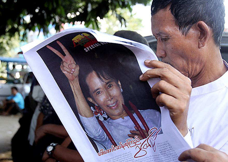 A member of opposition leader Aung San Suu Kyi's National League for Democracy reads a copy of local journal covered with her portrait outside the NLD headquarters Monday, Nov. 15, 2010 in Rangoon, Burma. Suu Kyi began the nuts and bolts work of reviving her political movement Monday, consulting lawyers about having her now-disbanded party declared legal again, her spokesman said. (AP Photo/Khin Maung Win)