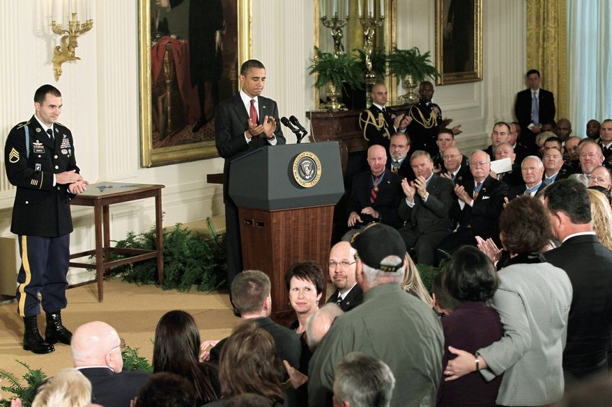 President Barack Obama and Army Staff Sgt. Salvatore Giunta acknowledge the parents of two soldiers rescued by the Medal of Honor winner. His parents, Steven and Rose Giunta, of Hiawatha, Iowa, are seated at center.
