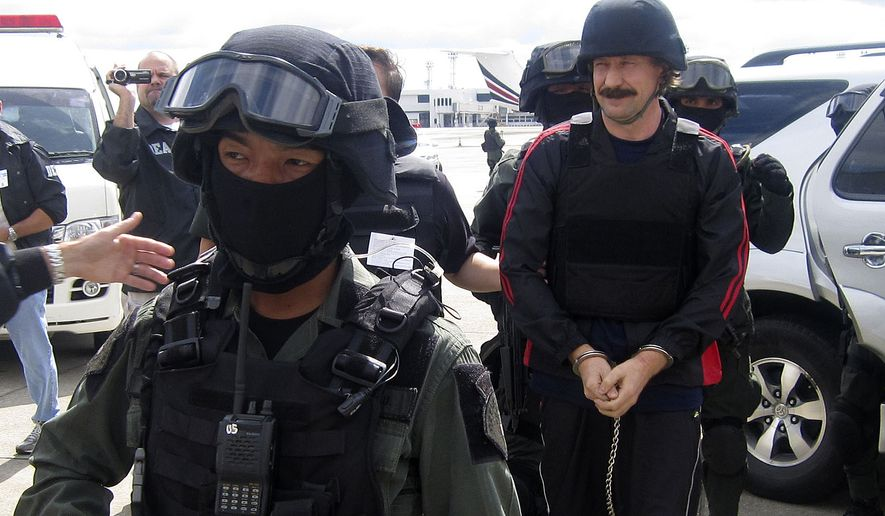Purported Russian arms trafficker Viktor Bout, right, escorted by Thai police commandos, arrives at Don muang airport in Bangkok on Tuesday, Nov. 16, 2010. Thailand extradited Mr. Bout to the U.S. on Tuesday to face terrorism charges. (AP Photo)