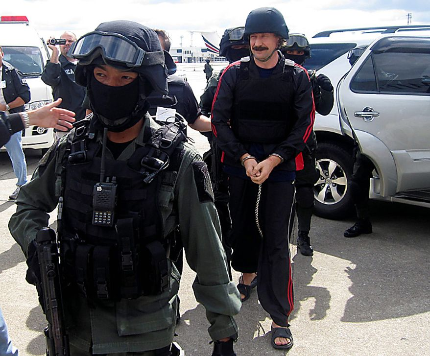 Alleged Russian arms trafficker Viktor Bout, right, escorted by Thai police commando,  arrives at Don muang airport in Bangkok on Tuesday Nov. 16, 2010.  Thailand extradited accused Bout to the U.S. on Tuesday to face terrorism charges, siding with Washington in a tug of war with Moscow over whether to send him to stand trial or let him go home. (AP Photo)