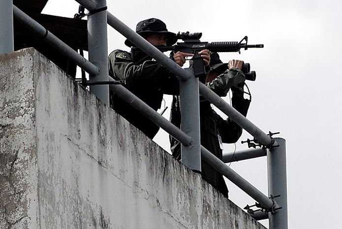 Armed commando officers stand by as the motorcade of accused Russian arms dealer arrived at Don Muang Airport in Bangkok on Tuesday Nov. 16, 2010.  The Thai government extradited accused Russian arms trafficker Viktor Bout to the United States on Tuesday to face terrorism charges, rejecting heavy pressure from Moscow for him to be freed. (AP Phoot/Sakchai Lalit)