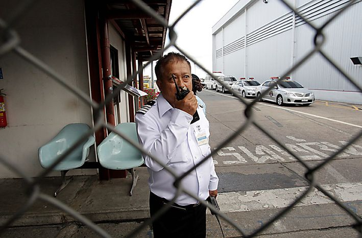 A Thai airport officer talks on radio as he blocked the media from entering the airport after Viktor Bout's motorcade arrived at Don Muang airport in Bangkok on Tuesday Nov. 16, 2010. The Thai government extradited accused Russian arms trafficker Viktor Bout to the United States on Tuesday to face terrorism charges, rejecting heavy pressure from Moscow for him to be freed. (AP Photo/Sakchai Lalit)
