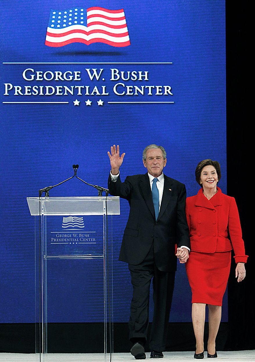 Former President George W. Bush, left, waves as he and his wife Laura Bush take the stage before the ground breaking ceremony for the President George W. Bush Presidential Center at SMU in Dallas, Tuesday, Nov. 16, 2010. (AP Photo/LM Otero)