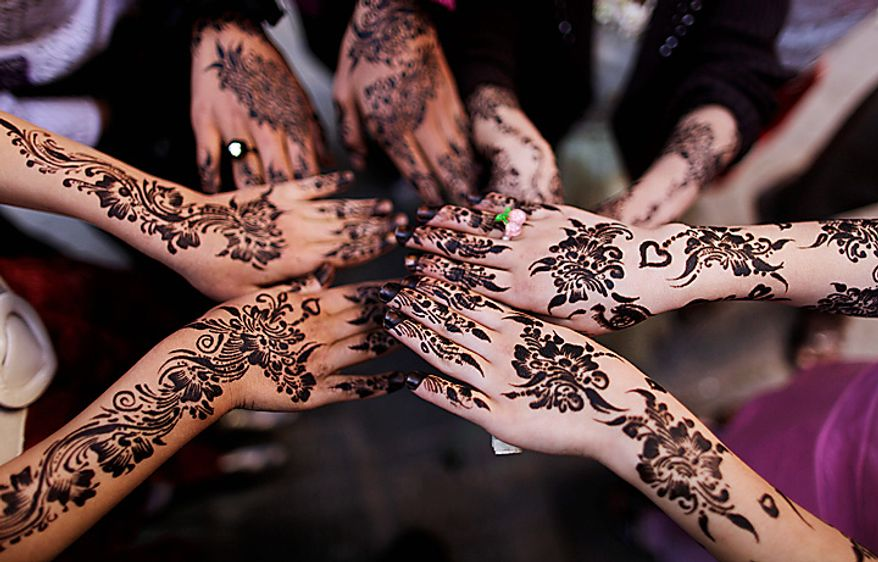 Yemeni girls display their hands painted with henna paste while playing in an alley of the old city, on the first day of the Muslim holiday of Eid al-Adha, or Feast of the Sacrifice, in Sanaa, Yemen, Tuesday, Nov. 16, 2010. (AP Photo/Muhammed Muheisen)