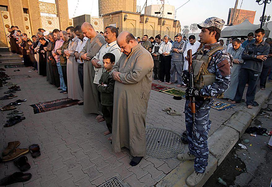 Iraqi Sunni Muslims gather for prayers as an Iraqi policeman stands guard on the first day of Eid al-Adha in Baghdad, Iraq, Tuesday, Nov. 16, 2010. Muslims around the world gathered on Tuesday to celebrate Eid al-Adha, or the Feast of Sacrifice. (AP Photo/Karim Kadim)