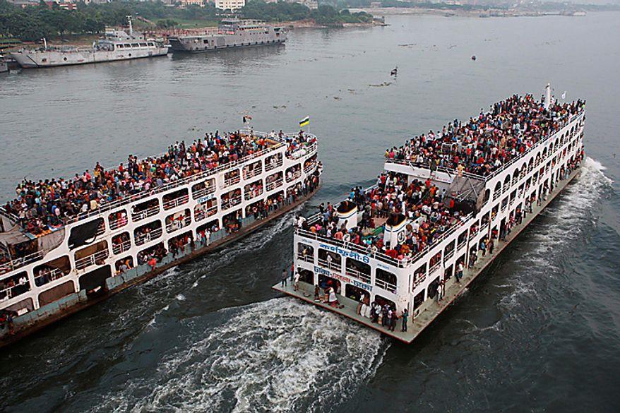 Hundreds of Bangladeshi passengers headed to the southern districts to celebrate Eid al-Adha travel in overcrowded ferries through the Buriganga river in Dhaka, Bangladesh, Tuesday, Nov.16, 2010.(AP Photo/Pavel Rahman)
