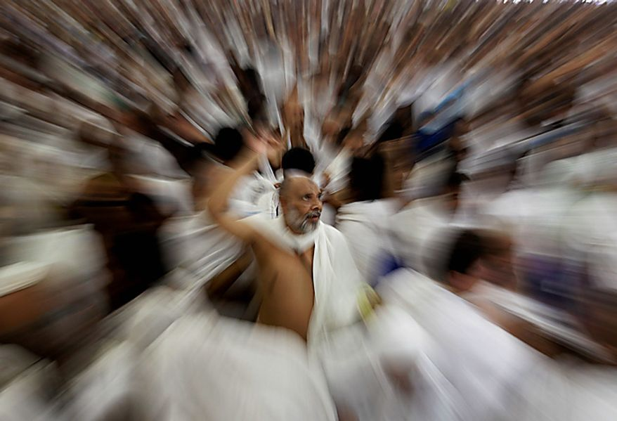 """Muslim pilgrims cast stones at a pillar, symbolizing the stoning of Satan, in a ritual called """"Jamarat,"""" the last rite of the annual hajj, in Mina near the Saudi holy city of  Mecca, Saudi Arabia, Tuesday, Nov. 16, 2010. The last stage of the annual Hajj pilgrimage, the symbolic stoning of the devil, began on Friday. The first day of stoning also marks the start of the Islamic holiday of Eid al-Adha, or feast of sacrifice, when Muslims around the world slaughter sheep and cattle in remembrance of Abraham's near-sacrifice of his son. (AP Photo/Hassan Ammar)"""