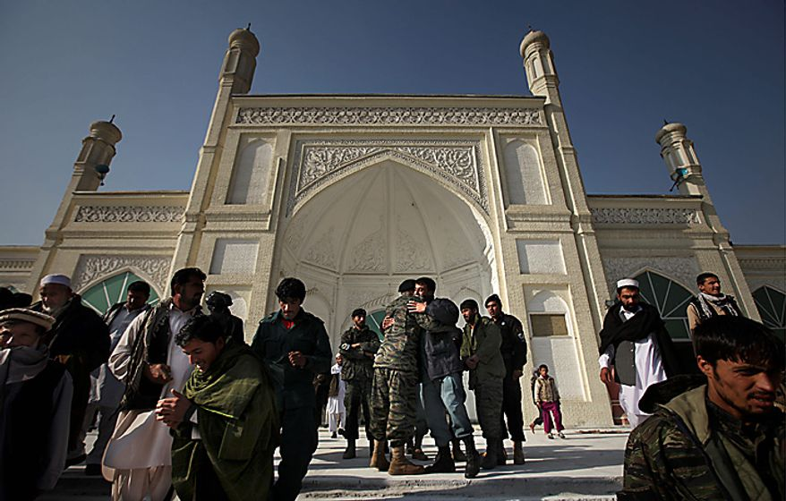 Afghan soldiers greet each other as they come out of a mosque after offering Eid al-Adha prayers in Kabul, Afghanistan, Tuesday, Nov. 16, 2010.  Muslims worldwide celebrate Eid al-Adha, or the Feast of the Sacrifice by sacrificial killing of livestock to commemorate the religious story of Abraham. (AP Photo/Altaf Qadri)