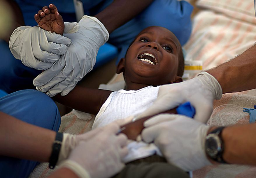 A child with cholera symptoms is treated by volunteer American doctors at a hospital in Archaie, Haiti, Monday Nov. 15, 2010. Nearly 1,000 people have been killed and thousands have been hospitalized for cholera across Haiti, with symptoms including serious diarrhea, vomiting and fever. (AP Photo/Ramon Espinosa)