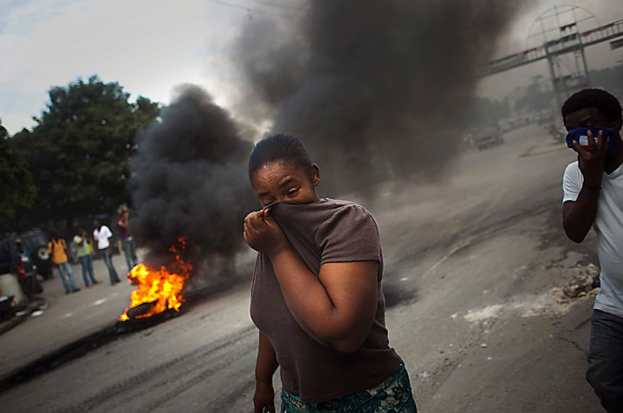 A woman covers her face from the smoke of burning tires set up by demonstrators in Port-au-Prince, Haiti, Monday, Nov. 15, 2010. Students in the capital protested burning tires and throwing stones at police, following demonstrations that began early Monday in the northern city of Cap-Haitien where protesters attacked with stones a U.N. base of Nepalese peacekeepers, whom they hold  responsible for the outbreak of cholera that has killed around 1,000 people in three weeks. (AP Photo/Emilio Morenatti)