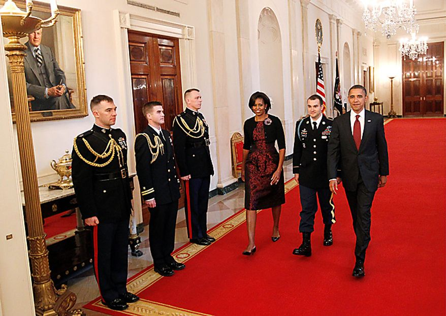 President Barack Obama and first lady Michelle Obama walk down the Cross Hall of the White House in Washington, Tuesday, Nov. 16, 2010, with Army Staff Sgt. Salvatore Giunta, before presenting him with the Medal of Honor during a ceremony in the East Room . Giunta, from Hiawatha, Iowa, is the first living veteran of the wars in Iraq and Afghanistan to receive the award. (AP Photo/Charles Dharapak)