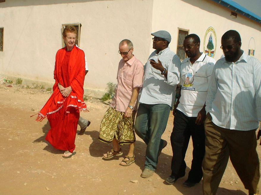 ASSOCIATED PRESS PHOTOGRAPHS British seafarers Paul and Rachel Chandler talk with local leaders in Adado, Somalia, after being released Sunday by pirates. The couple later flew to Mogadishu en route to Kenya and then home.