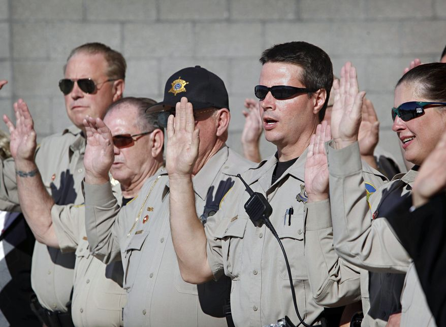 """ASSOCIATED PRESS Fifty-six new members of the Maricopa County sheriff's """"Immigration Posse"""" are sworn in Phoenix. Sheriff Joe Arpaio has deputized nearly 3,000 posse members since 1993. He is fighting U.S. Justice Department accusations that he discriminates against Hispanics."""